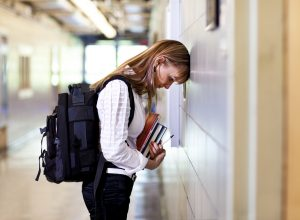 Young woman student under stress at school, thinking about her problems with her head to the wall.