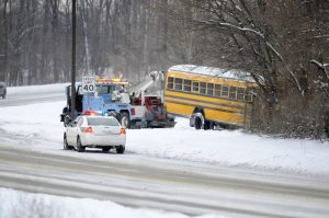 A school bus slides off from a slippery road.